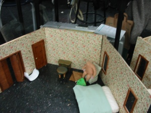 Martha starts to build props, add doors- her dad made the small green table and stool- it has a tiny drawer that works